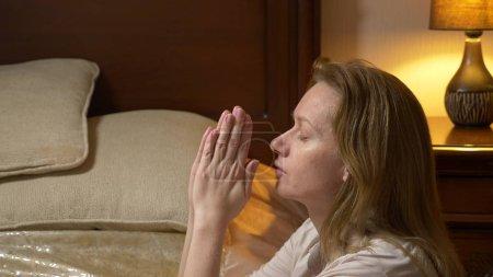 Photo pour Une jeune femme blonde priant avant d'aller au lit . - image libre de droit