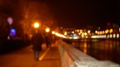 People stroll along the embankment strewn with evening lights. blur. bokeh