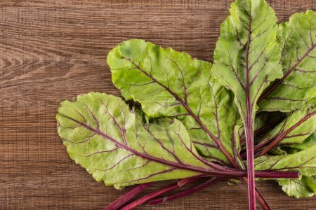 Fan of beet greens flatlay isolated on brown wood background top view fresh young leave
