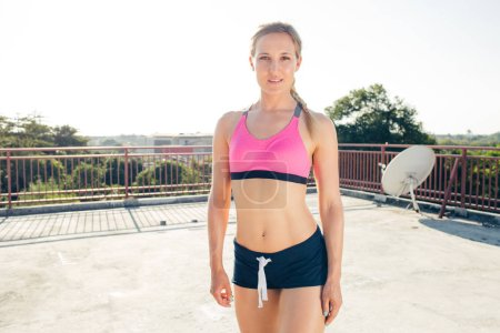 smiling young young sportswoman standing and looking at camera on rooftop