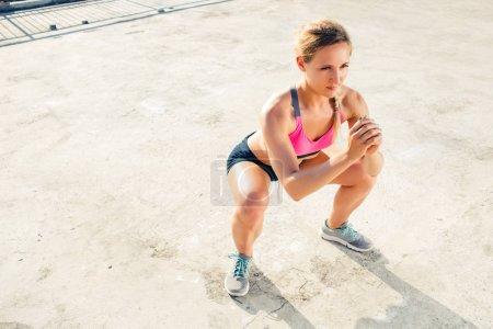 Photo pour Vue grand angle de jeune sportive faisant de l'exercice de squat sur le toit - image libre de droit