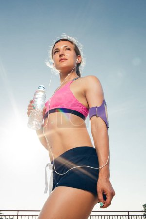 low angle view of young sportswoman in earphones with smartphone in running armband case holding bottle of water against blue sky