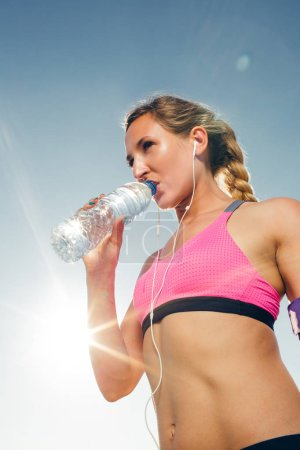 low angle view of young sportswoman in earphones drinking water from bottle against blue sky