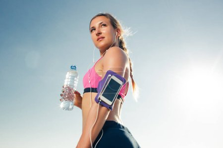 young sportswoman in earphones with smartphone in armband sport case holding bottle of water against blue sky