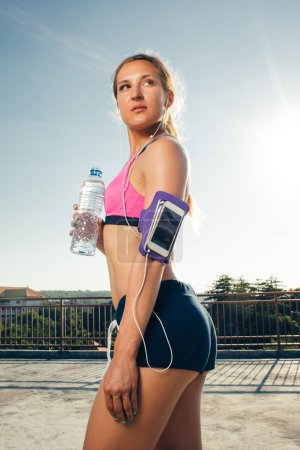 attractive sportswoman in earphones with smartphone in  running armband case holding bottle of water on rooftop
