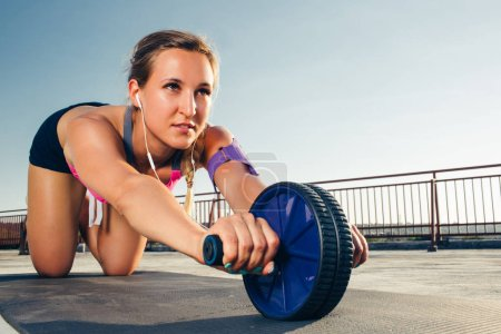 young sportswoman in earphones with smartphone in running armband case doing exercise with abs roller on fitness mat on rooftop