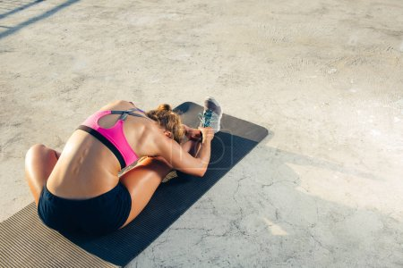 rear view of sportswoman stretching on fitness mat on rooftop