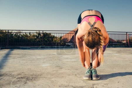 Photo for Female athlete in earphones stretching on rooftop - Royalty Free Image