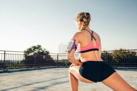 rear view of sportswoman in earphones with smartphone in running armband case stretching on rooftop