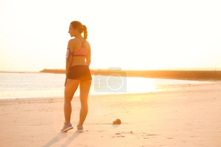 Photo for Silhouette of young sportswoman with smartphone in running armband case standing on beach against sunlight - Royalty Free Image
