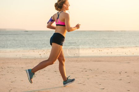 smiling sportswoman in earphones with smartphone in running armband case jogging on beach with sea behind