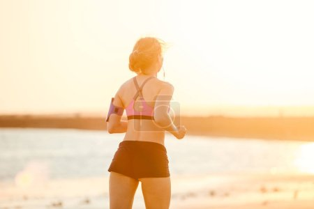 rear view of sportswoman in earphones with smartphone in running armband case jogging on beach against sunlight