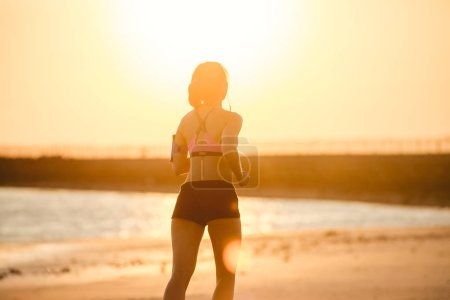 rear view of silhouette of sportswoman in earphones with smartphone in running armband case jogging on beach against sunlight
