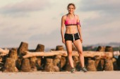 young female athlete in earphones with smartphone in running armband case standing on sandy beach