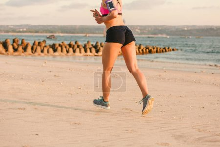 cropped shot of sportswoman with smartphone in running armband case jogging on beach with sea behind