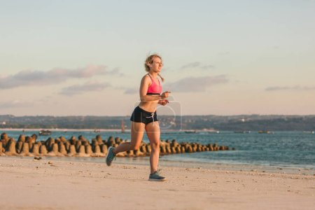 sportswoman in earphones with smartphone in running armband case jogging on beach with sea behind
