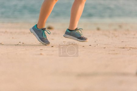 cropped shot of female jogger in sneakers running on sandy beach with sea behind