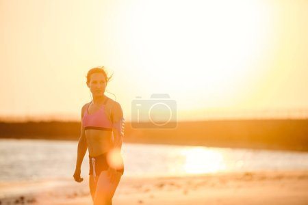 silhouette of sportswoman in earphones with smartphone in running armband case on beach against sunlight