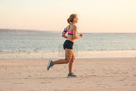 side view of sportswoman in earphones with smartphone in running armband case jogging on beach with sea behind