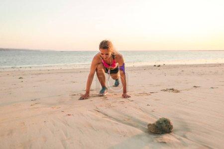 Photo pour Femme sportive dans des écouteurs avec smartphone dans un étui brassard s'exerçant sur une plage de sable avec mer derrière - image libre de droit