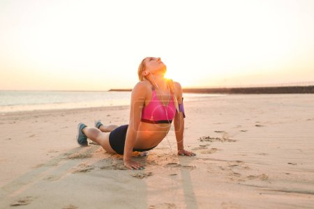 young sportswoman in earphones with smartphone in armband case exercising on sandy beach against sunlight