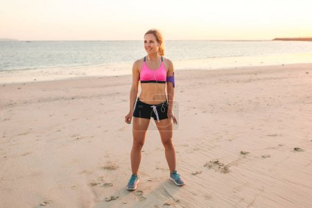 smiling sportswoman in earphones with smartphone in armband case standing on sandy beach with sea behind