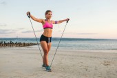 young sportswoman in earphones with smartphone in armband case doing exercise with stretching band on beach