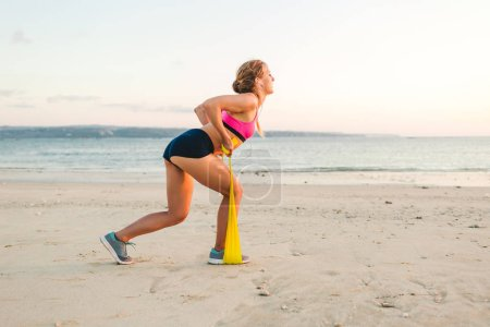 side view of sportswoman doing exercise with stretching band on beach
