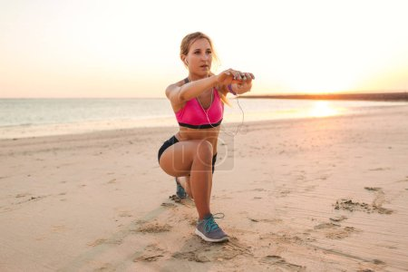 Photo for Young sportswoman in earphones with smartphone in armband case doing exercise on beach - Royalty Free Image