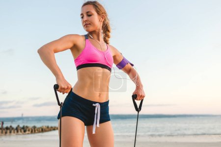 sportswoman in earphones with smartphone in armband case doing exercise with stretching band on beach with sea behind