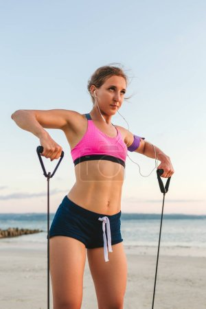 Photo for Female athlete in earphones with smartphone in armband case doing exercise with stretching band on beach - Royalty Free Image