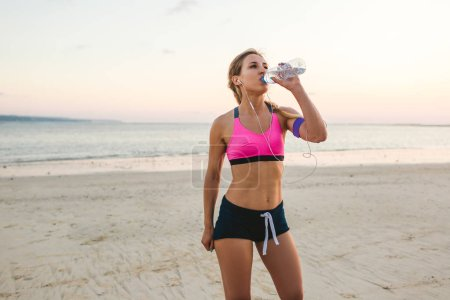 sportswoman in earphones with smartphone in armband case drinking water from bottle on beach with sea behind