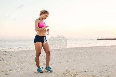 attractive sportswoman in earphones with smartphone in armband case holding bottle of water on beach with sea behind
