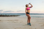 young sportswoman in earphones with smartphone in armband case drinking water from bottle on beach with sea behind