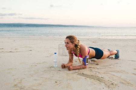 sportswoman in earphones with smartphone in armband case and bottle of water doing plank on sandy beach