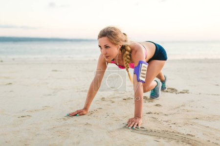 sportswoman in earphones with smartphone in armband case doing exercise on sandy beach