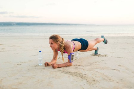 young sportswoman in earphones with smartphone in running armband case and bottle of water doing plank on sandy beach