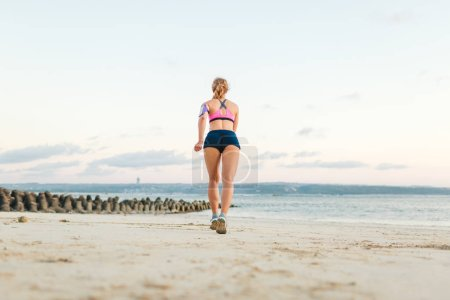 rear view of sportswoman with smartphone in running armband case jogging on sandy beach
