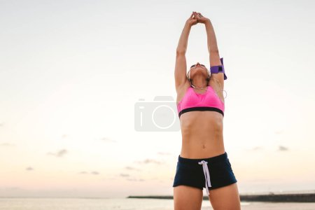 low angle view of sportswoman in earphones with smartphone in running armband case doing exercise on beach