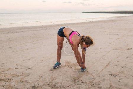 female athlete in earphones doing exercise on beach