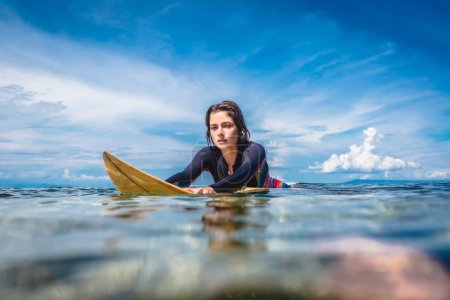 portrait of young sportswoman in wetsuit on surfing board in ocean at Nusa dua Beach, Bali, Indonesia