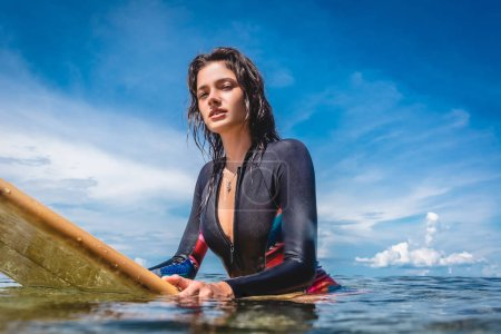portrait of sportswoman in wetsuit on surfing board in ocean at Nusa dua Beach, Bali, Indonesia