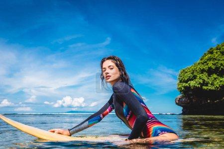 side view of pretty sportswoman in wetsuit on surfing board in ocean at Nusa dua Beach, Bali, Indonesia