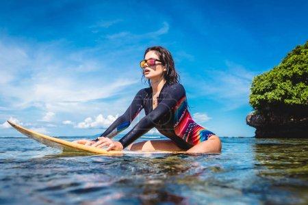 Photo pour Sportive en combinaison et lunettes de soleil sur planche de surf dans l'océan à Nusa dua Beach, Bali, Indonésie - image libre de droit