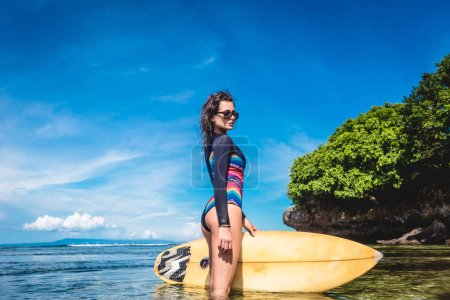 beautiful young woman in wetsuit and sunglasses with surfboard posing in ocean at Nusa dua Beach, Bali, Indonesia