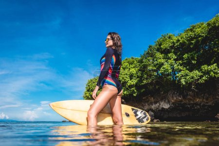attractive woman in wetsuit and sunglasses with surfboard posing in ocean at Nusa dua Beach, Bali, Indonesia