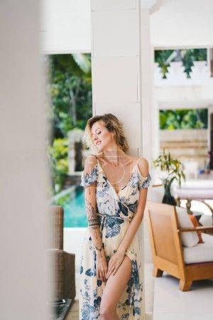 portrait of beautiful tattooed woman in dress standing at villa