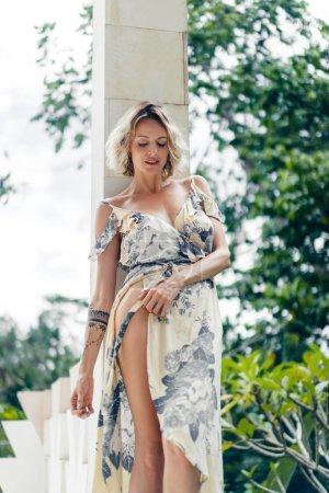 Photo pour Jolie femme blonde en robe debout à la terrasse de la villa avec des plantes vertes sur le fond - image libre de droit