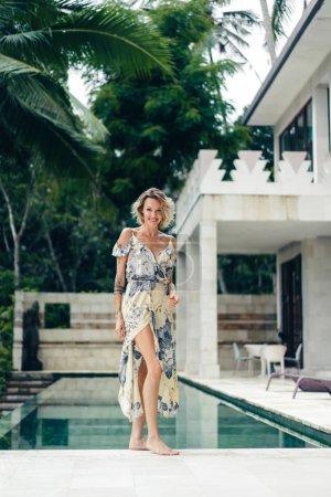 Photo pour Jolie femme souriante en robe debout près de la piscine à la terrasse de la villa - image libre de droit