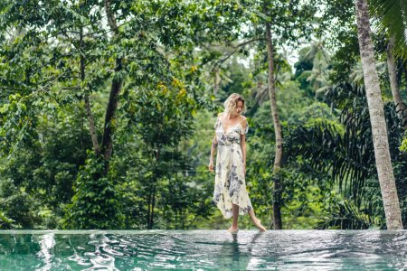 attractive blond woman in dress walking near swimming pool with green plants on background, ubud, bali, indonesia